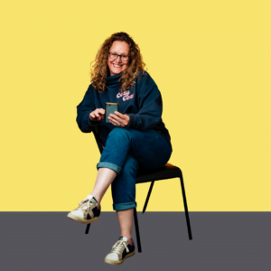 Woman sitting on chair with phone in hand with yellow background