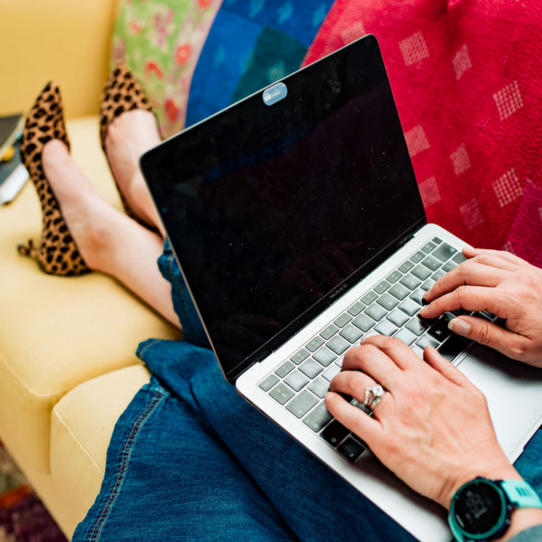 Typing on laptop while sitting on sofa