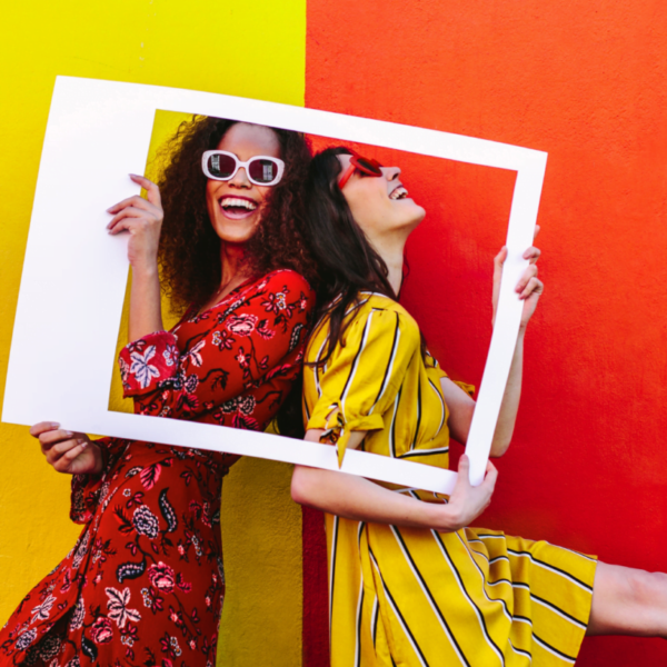 girls holding a picture frame against a yellow and orange background